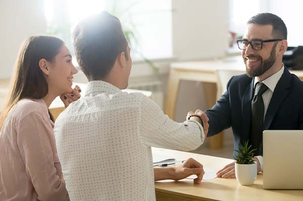 couple shaking hands with banker